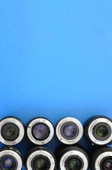 Varias lentes fotográficas se encuentran sobre un fondo azul brillante. espacio para texto