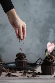 Varias magdalenas o cupcakes con crema en forma de chocolate en la mesa blanca. una tarjeta en forma de corazón para el día de san valentín. la mano de una mujer desmenuza el chocolate rallado en un pastel.