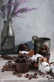Varias magdalenas o cupcakes con crema en forma de chocolate en la mesa blanca. vela festiva arde en un pastel de chocolate. hay chispas de chocolate esparcidas cerca