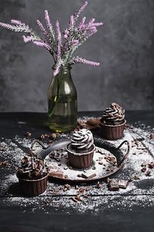 Varias magdalenas o cupcakes con crema en forma de chocolate en la mesa negra. el azúcar en polvo se esparce sobre las tortas.