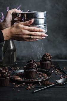 Varias magdalenas o cupcakes con crema en forma de chocolate en la mesa negra. la mano de una mujer desmenuza el azúcar en polvo en un pastel.