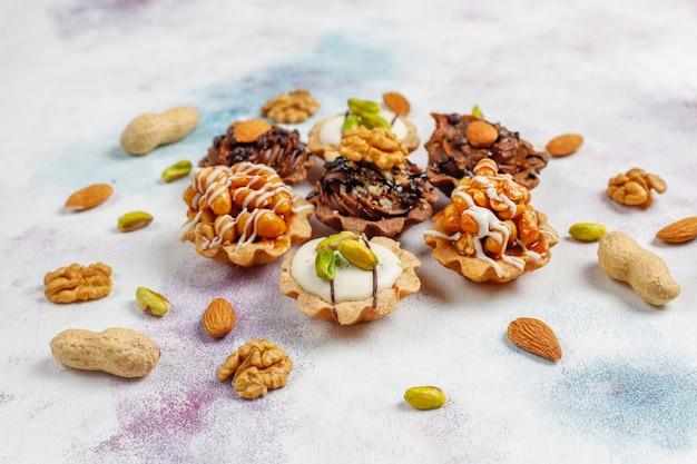 Varias mini tartaletas caseras con nueces y crema de chocolate.