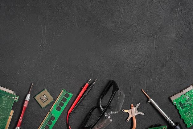 Varias partes de la computadora; multímetro digital y gafas de seguridad sobre fondo negro.