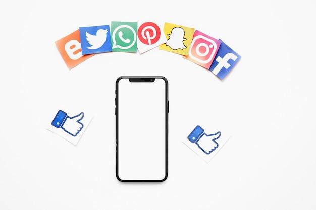 Varias redes sociales y como iconos cerca de teléfono móvil con pantalla en blanco