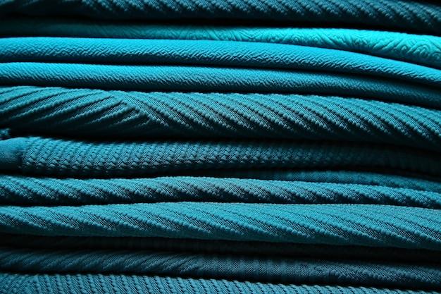 Varias telas de diseño de color turquesa dentro de una tienda textil