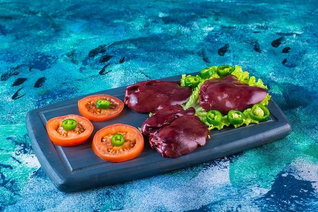 Varias verduras e hígado de pollo en la bandeja de madera