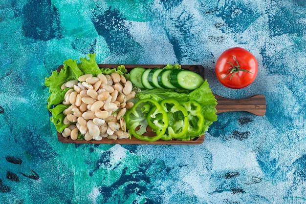 Varias verduras y frijoles a bordo en azul.