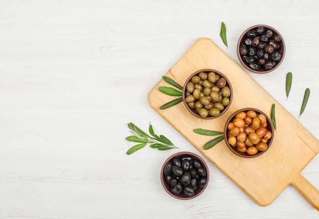 Variedad de aceitunas con hojas de olivo en cuencos de arcilla y tabla de cortar en madera blanca, plana.