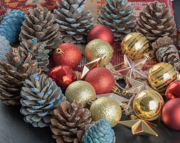 Variedad de adornos para árboles de navidad en un trozo de alfombra étnica de patrón rojo