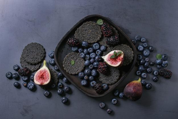 Variedad de bayas e higos con galletas negras.