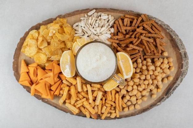 Variedad de bocadillos y vaso de cerveza en pieza de madera