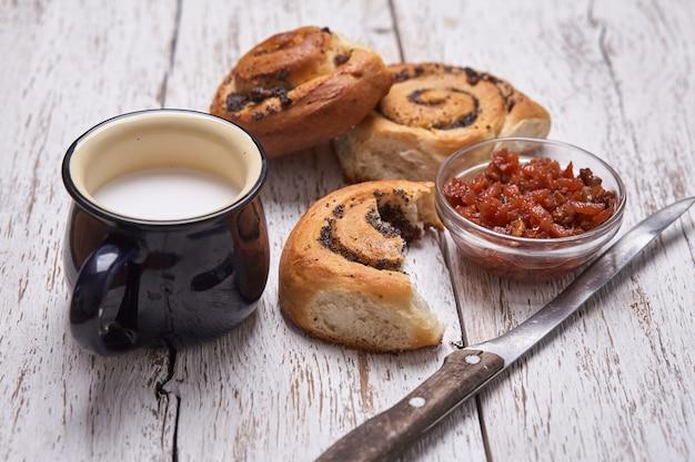 Variedad de bollos caseros de hojaldre de canela servidos con taza de leche, mermelada, mantequilla como desayuno sobre tabla blanca de mesa de madera