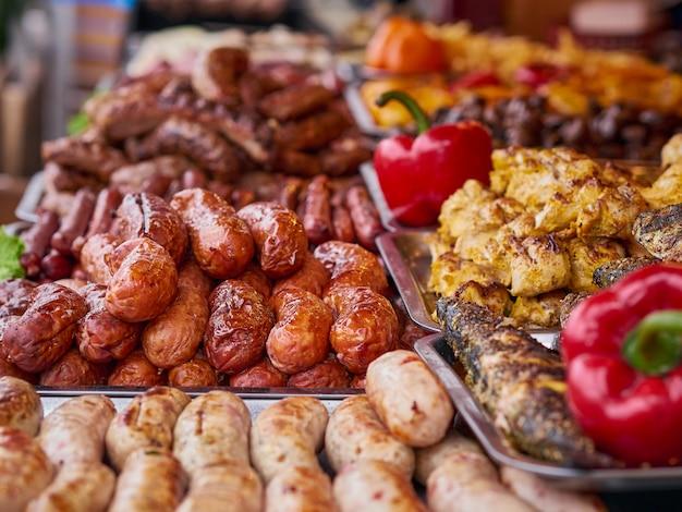 Variedad de carnes a la parrilla en la tienda de comida callejera, chorizos y pimientos rojos