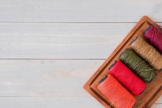 Variedad de carretes de colores brillantes en bandeja de madera sobre el escritorio blanco