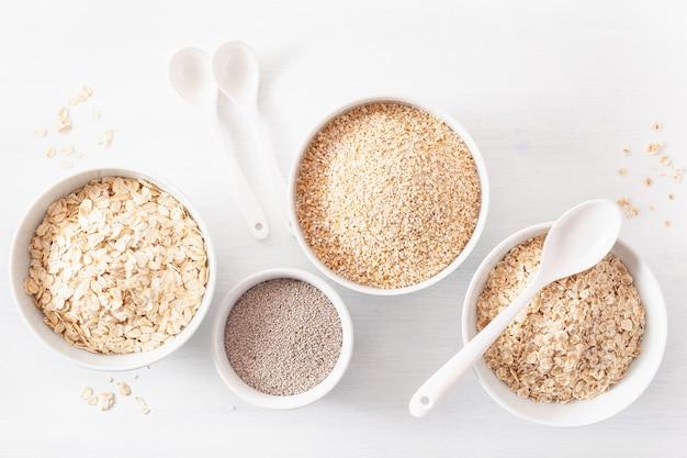 Variedad de cereales crudos para el desayuno. copos de avena y corte de acero, cebada, chía. ingredientes saludables