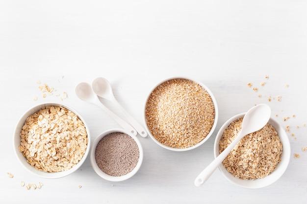 Variedad de cereales crudos para el desayuno. copos de avena y corte de acero, cebada, semillas de chía. ingredientes saludables