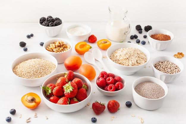 Variedad de cereales crudos, frutas y nueces para el desayuno. copos de avena y corte de acero, cebada, nuez, chía, albaricoque, fresa. ingredientes saludables