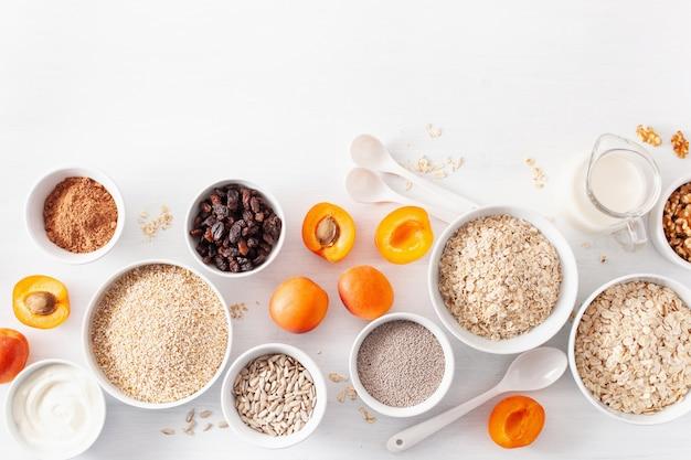 Variedad de cereales crudos, frutas y nueces para el desayuno. copos de avena y corte de acero, cebada, nuez, chía, albaricoque. ingredientes saludables