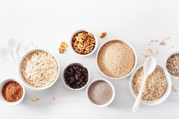 Variedad de cereales crudos y nueces para el desayuno. copos de avena y corte de acero, cebada, nuez, chía, pasas. ingredientes saludables
