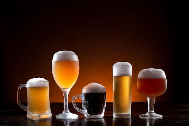 Variedad de cervezas en diferentes vasos sobre base de madera.
