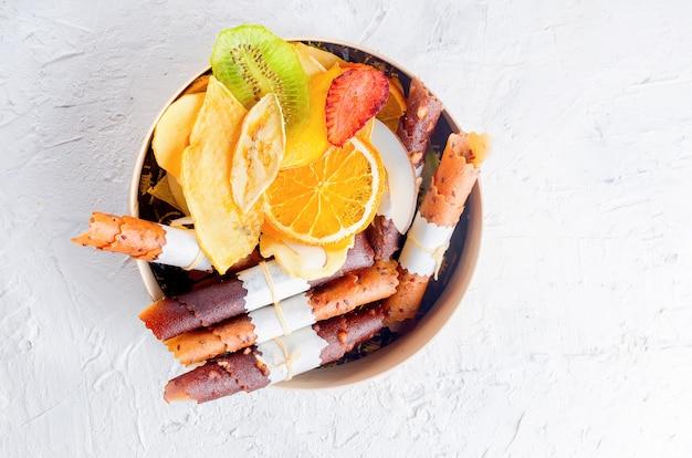 Variedad de chips de frutas en caja redonda de madera.