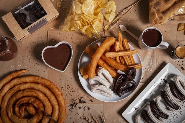 Variedad de churros tradicionales con azúcar granulada y chocolate sobre una mesa de papel artesanal. vista superior. productos típicos de la churreria