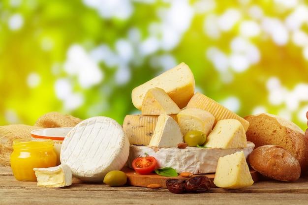 Variedad de composición de tipos de queso sobre tabla de madera.