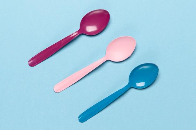 Variedad de cucharas de colores sobre fondo azul. Foto gratis