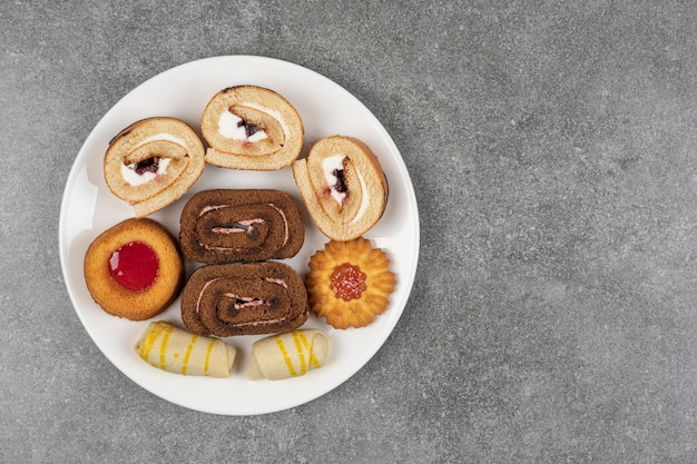Variedad de deliciosas galletas en plato blanco