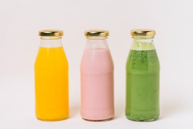 Variedad de deliciosos batidos de frutas en botellas.
