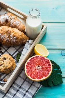 Variedad de desayunos saludables en bandeja de madera con cítricos.