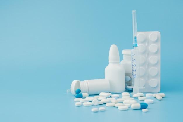 Variedad dispersa de píldoras, medicamentos, esterilización, botellas, termómetro, jeringa y carrito de compras vacío sobre fondo azul. concepto de compras de farmacia