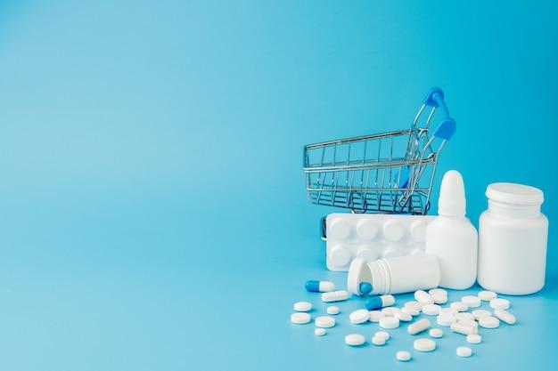 Variedad dispersa de píldoras, medicamentos, esterilización, botellas, termómetro, jeringa y carrito de compras vacío sobre fondo azul.