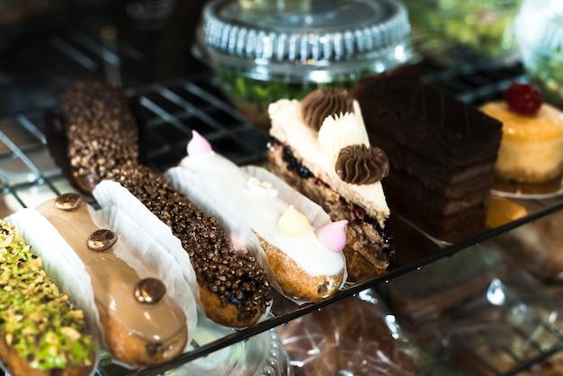 Variedad de eclairs y deliciosos pasteles de repostería en la vitrina.