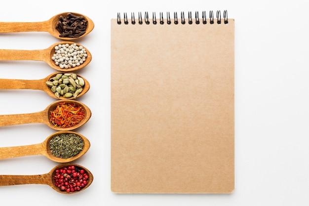 Variedad de especias en cucharas de madera y cuaderno.