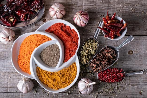Variedad de especias y hierbas de exóticos colores indios, sobre la mesa de la cocina.