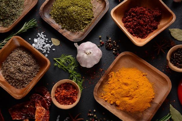 Variedad de especias y hierbas en la mesa de la cocina. coloridas diversas hierbas y especias para cocinar sobre fondo oscuro