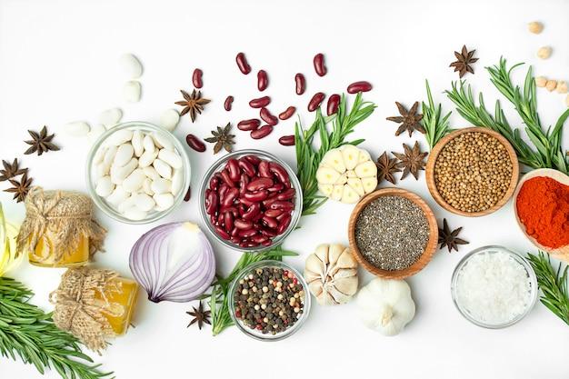 Una variedad de especias y hierbas en una mesa de luz. mesa de cocina vista desde arriba. ingredientes para cocinar. mesa mesa menú.