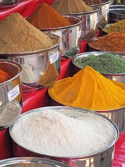 Variedad de especias en tazones azules para la venta. herencia de la india