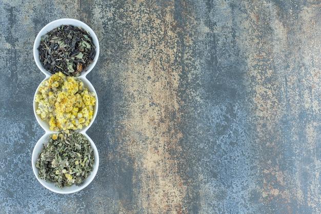 Variedad de flores secas y hojas de té en tazones blancos.
