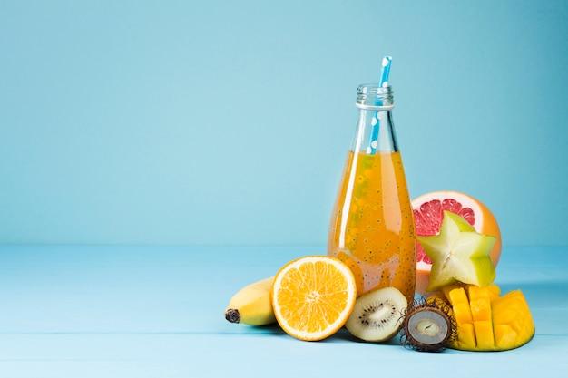 Variedad de fruta y jugo sobre fondo azul