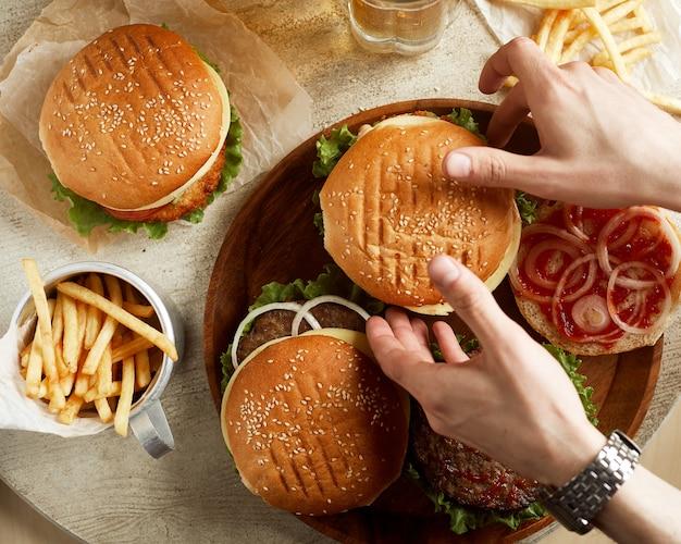 Variedad de hamburguesas con papa frita y vaso de cerveza.