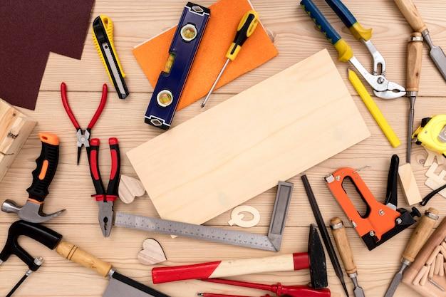 Variedad de herramientas de carpintería con tablón de madera de espacio de copia