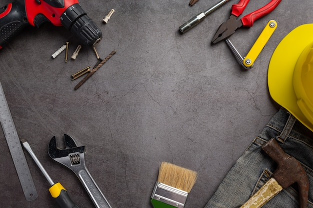 Variedad de herramientas útiles sobre fondo oscuro, concepto de fondo del día del trabajo Foto gratis