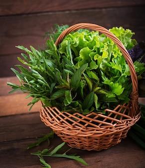 Variedad de hierbas orgánicas frescas (lechuga, rúcula, eneldo, menta, lechuga roja y cebolla) en estilo rústico.