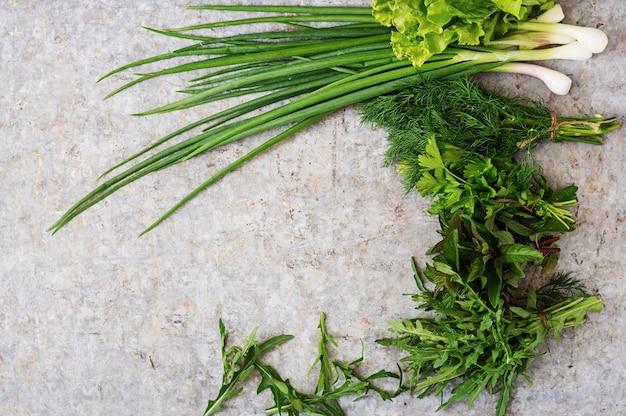 Variedad de hierbas orgánicas frescas (lechuga, rúcula, eneldo, menta, lechuga roja y cebolla) sobre fondo gris en estilo rústico. vista superior