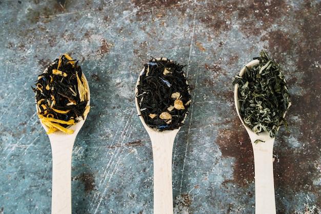 Variedad de hierbas de té en cucharas vista superior