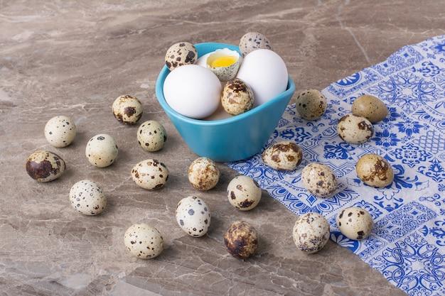 Variedad de huevos en una taza sobre superficie gris