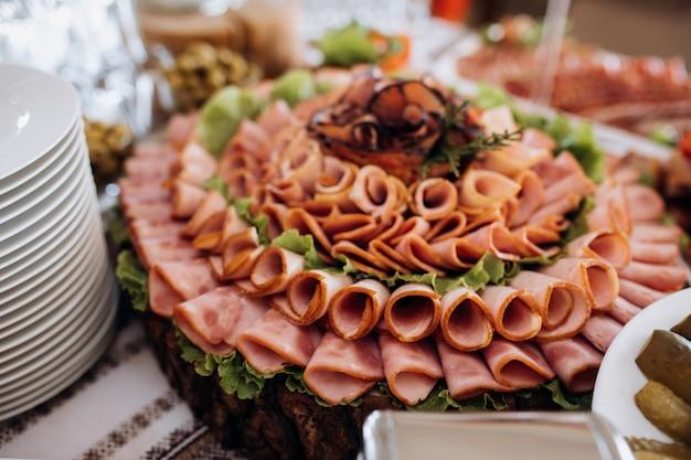 Variedad de jamón loncheado y decorado con ensalada.