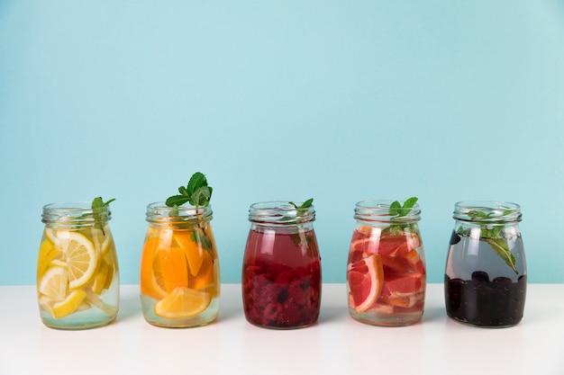 Variedad de jugo de fruta fresca con fondo azul claro.